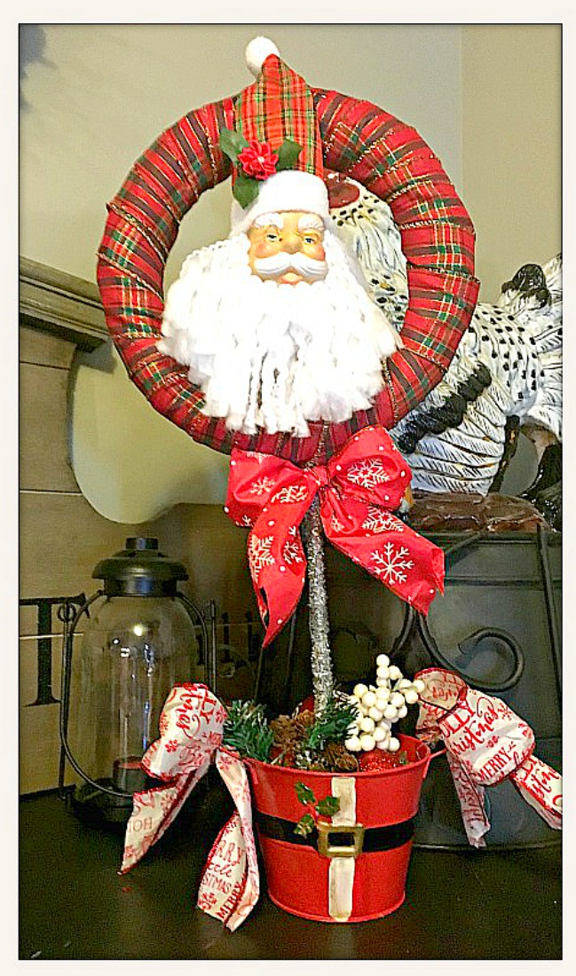 COWGIRL CHRISTMAS DECOR Tartan Plaid Ribbon Wreath with Santa & Bows in Metal Santa Belly Pot Filled with Ornaments and Pine Cones